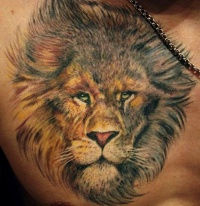 Realistic lion face tattoo on chest