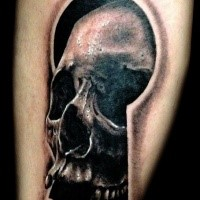 3D style black ink leg tattoo of large keyhole with human skull