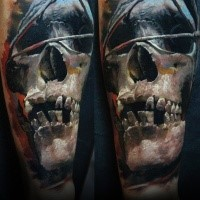 3D style colored arm tattoo of tribal skull with triangle
