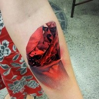 3D style colored forearm tattoo of pure red diamond