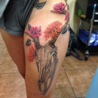 3D style natural looking colored animal skull tattoo on thigh combined with various flowers