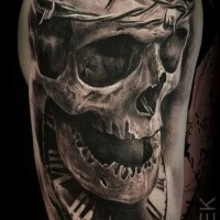 3D style upper arm tattoo of human skull with barbed wire and clock by Eliot Kohek