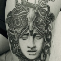 3D very realistic looking black ink sad Medusa head tattoo on thigh with snaked and animal skull