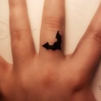 Tatuaje de silueta negra de murciélago en el dedo