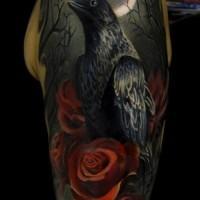 Tattoo von wunderbarem schwarzem Raben mit roten Rosen und Mond am Oberarm