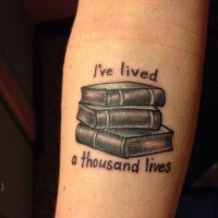 Black-and-white books with quote tattoo on forearm