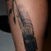Black-and-white eagle feather on rope tattoo
