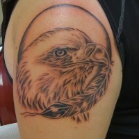 Black-and-white eagle head and feather tattoo on upper arm