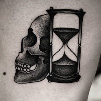 Black dotwork skull with hourglass tattoo on side