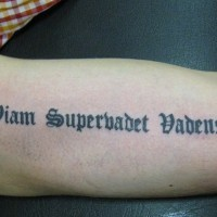 Black gothic-lettered quote tattoo on arm
