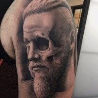 Black grey arm tattoo of half human skull with viking