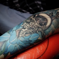 Blue flower and black skull tattoo on arm
