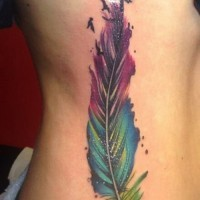 Blurred vivid-colored feather bird tattoo on side