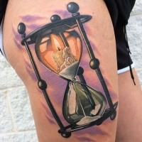 Colorful hourglass with cahdle thigh tattoo