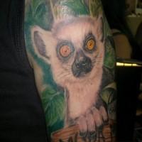 Oberarm Farbtattoo mit coolem Lemur und Holztisch in Tropenblättern