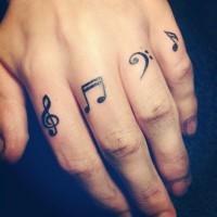 fresco piccolo segni misicali inchiostro nero tatuaggio su dita