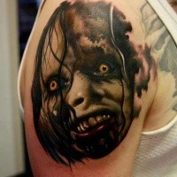 Creepy looking colored upper arm tattoo of monster portrait