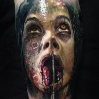 Creepy modern looking leg tattoo of zombie monster face
