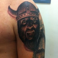 Crying Viking head tattoo on shoulder