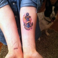 Cute little colored anchor on purple background tattoo on forearm