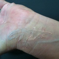 Cute white-ink feather tattoo on wrist