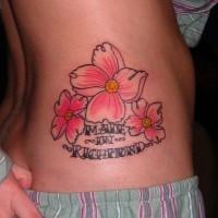 Tatuaje en el costado, flores exquisitas con inscripción
