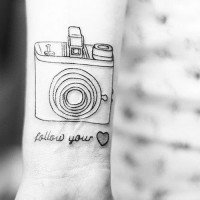 Follow your heart quote with a camera tattoo on arm