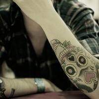 Funny colorful muerte skull tattoo on outer arm