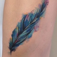 Great blurred colorful feather tattoo on thigh