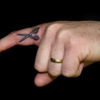 Tatuaje de tijeras pequeñas en el dedo