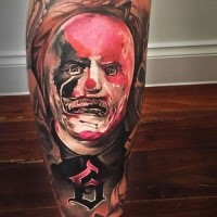 Horror movie style colored leg tattoo of man with creepy mask