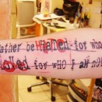 Tatuaje en el antebrazo, inscripción estupenda tachada, colores negro y rojo