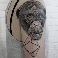 Interesting uncolored chimpanzee head with abstract figure tattoo on upper arm