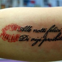Italian quote and red kiss tattoo on arm