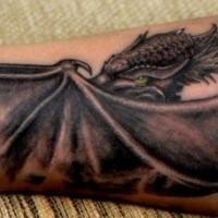 Large black green-eyed dragon tattoo on forearm