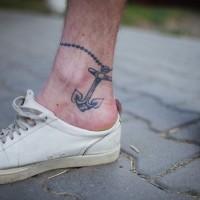 piccola bianca e nera ancora su catena tatuaggio su caviglia