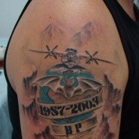 Military memorial style colored upper arm tattoo of big plane with lettering