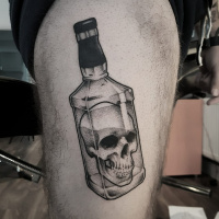 Nice black and white skull in whiskey bottle tattoo on thight
