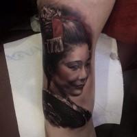 Tatuaggio con il braccio superiore colorato di un ritratto di geisha