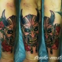 Old school style colored arm tattoo of monster mask with flowers