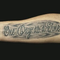 Tatuaje en el antebrazo, frase en el fordo negro