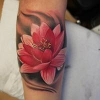 Pretty pink lotus flower on black background tattoo on arm