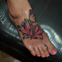 Pretty vivid-colored lily flower and butterfly tattoo on foot