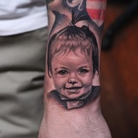 Realistic american classic baby portrait tattoo on arm