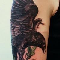 Tattoo von realistischem schwarzem Raben auf dem Zweig am Oberarm