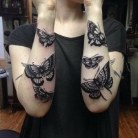 Realistic girly black-ink butterfly tattoo on forearms