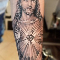 Realistic religious black-and-white Jesus with shining heart tattoo on forearm