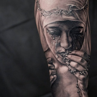 Realistic religious theme sleeve tattoo