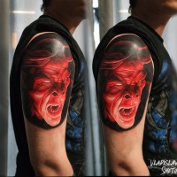 Red demon face tattoo on shoulder