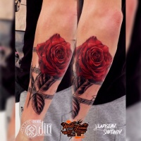 Red rose and music notes tattoo on forearm